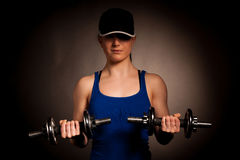 Beautiful young woman working out with dumbels in fitness gym. Beautiful young woman posing after working out with dumbels in fitness gym isolated Stock Photos