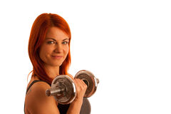 Beautiful young woman working out with dumbels in fitness gym. Smiling Stock Photos