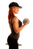 Beautiful young woman working out with dumbels in fitness gym. Beautiful young woman wearing hat working out with dumbels in fitness gym Stock Image