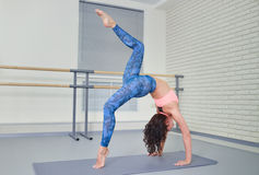 Beautiful young woman working out in fitness class, doing yoga exercise on mat, stretching, standing in Bridge Pose Stock Image