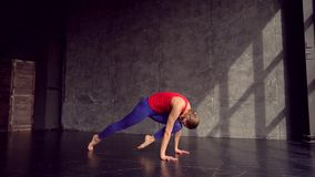 Beautiful young woman working out indoors, doing yoga exercise in the room with white walls, downward facing dog pose. Adho mukha svanasana sun salutation pose stock video