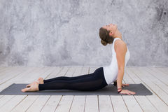 Beautiful young woman working out indoors, doing yoga exercise in the room with white walls, downward facing dog pose Royalty Free Stock Images