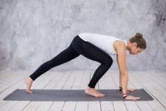 Beautiful young woman working out indoors, doing yoga exercise in the room with white walls, downward facing dog pose Stock Image