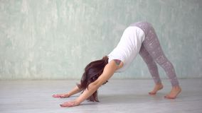 Beautiful young woman working out indoors, doing yoga exercise in the room with white walls, downward facing dog pose. Adho mukha svanasan a, full length, side stock video