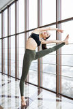 Beautiful young woman working out in luxury fitness center, doing yoga hasta padangusthasana Royalty Free Stock Images