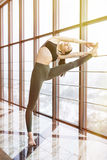 Beautiful young woman working out in luxury fitness center, doing yoga hasta padangusthasana Stock Photo