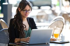 Beautiful Young Woman Working With Her Laptop While Having Breakfast In A Coffee Shop. Stock Photography