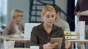 Beautiful young woman on the workplace using a digital tablet stock video