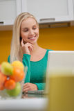 Beautiful young woman wotking on laptop. In her kitchen Royalty Free Stock Images