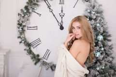 Beautiful young woman wrapped in a blanket over Christmas tree Stock Photography