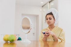 Beautiful, young woman wrapped in a towel spreading cream on her face. During this time it looks in the mirror. Calm royalty free stock photo