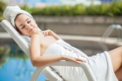 Beautiful young woman wrapped white towel  lying on sun bed at s. Wimming pool .lady sleep relaxing Sunbathe on poolside in spa Stock Images