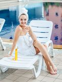 Beautiful young woman wrapped white towel sitting on sun bed app stock photos