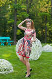 Beautiful young woman in a wreath of flowers and a bright dress sitting on the grass Portrait in nature, the joy of life, smile Royalty Free Stock Photography