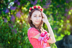 Beautiful young woman with wreath flowers walking in the garden Stock Photo