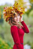 Beautiful young woman with a wreath of leaves on her head. Beautiful young woman smiling with a wreath of leaves on her head. Outdoor portrait in autumn park royalty free stock photos