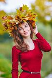 Beautiful young woman with a wreath of leaves on her head. Beautiful young woman smiling with a wreath of leaves on her head. Outdoor portrait in autumn park royalty free stock photo