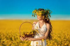 Beautiful young woman with wreath on long healthy hair over Yellow rape field landscape background. Attracive brunette girl with stock photos