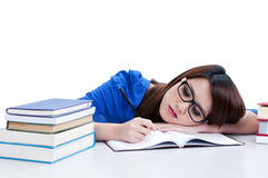 Beautiful young woman writing. Tired young student writing with head resting on arm, over white background Royalty Free Stock Photography