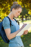 Beautiful young woman writing on clipboard at park Stock Photo