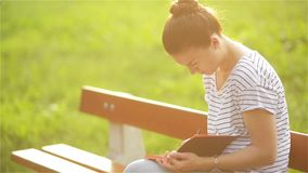 Beautiful young woman is writing a diary outdoors in the park, student studying on a bench in the park, Student girl stock video