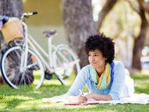 Beautiful young woman writing in her diary outdoors. Beautiful young woman writing in her diary in summer park Royalty Free Stock Image