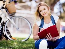 Beautiful young woman writing in her diary outdoors. Beautiful young woman writing in her diary in summer park Stock Photography