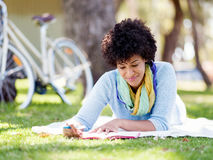 Beautiful young woman writing in her diary outdoors. Beautiful young woman writing in her diary in summer park Royalty Free Stock Photos