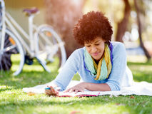 Beautiful young woman writing in her diary outdoors. Beautiful young woman writing in her diary in summer park Stock Photos