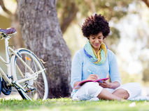 Beautiful young woman writing in her diary outdoors Stock Image