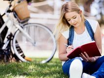 Beautiful young woman writing in her diary outdoors. Beautiful young woman writing in her diary in summer park Royalty Free Stock Images