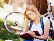 Beautiful young woman writing in her diary outdoors. Beautiful young woman writing in her diary in summer park Royalty Free Stock Photo