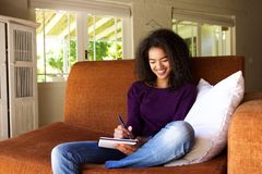 Beautiful young woman writing ideas in book. Portrait of a beautiful young woman writing ideas in book Stock Photography