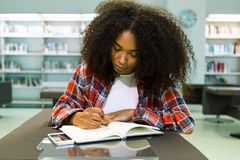 Beautiful young woman writing in a notebook in the library. Portrait of beautiful young woman writing in a notebook in the library Royalty Free Stock Photography