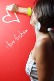 Beautiful young woman writing. On the red wall Royalty Free Stock Photos