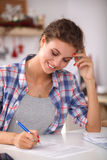 Beautiful young woman writing something in her Stock Image