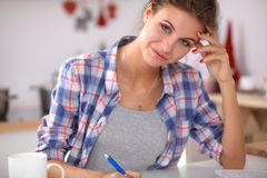 Beautiful young woman writing something in her Royalty Free Stock Images