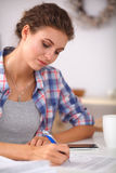 Beautiful young woman writing something in her Stock Photography