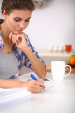 Beautiful young woman writing something in her Stock Photos
