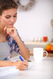 Beautiful young woman writing something in her Royalty Free Stock Photo