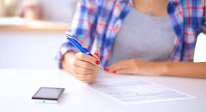 Beautiful young woman writing something in her Royalty Free Stock Image