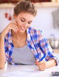 Beautiful young woman writing something in her note pad.  Stock Photos