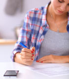 Beautiful young woman writing something in her note pad.  Royalty Free Stock Photos