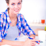 Beautiful young woman writing something in her note pad Royalty Free Stock Images