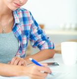 Beautiful young woman writing something in her note pad. Isolated Stock Photo