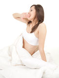 Beautiful young woman yawning in white bedding Stock Photo