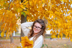 Beautiful young woman with yellow autumn wreath on bright backgr Stock Images