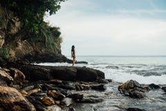 Beautiful young woman in yellow bikini standing on a rock on ocean shore. Beautiful young woman in yellow bikini standing on a rock ocean shore. Sexy girl Royalty Free Stock Images