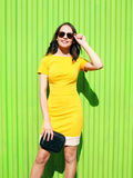 Beautiful young woman in yellow dress with black handbag clutch Royalty Free Stock Photos