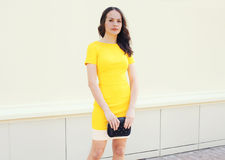 Beautiful young woman in yellow dress with black handbag clutch Stock Image